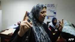 A Libyan woman raises her ink-stained finger after voting for Libya's General National Assembly at a polling station in Tripoli on July 7.