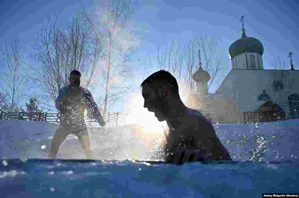 A man takes a dip in the settlement of Moskalenki in Russia's Omsk region.