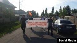 Участники митинга в Кара-Кульджинском районе с плакатом, на котором написано: «Руки прочь от Асылбека Жээнбекова!». 1 июня 2021 года.
