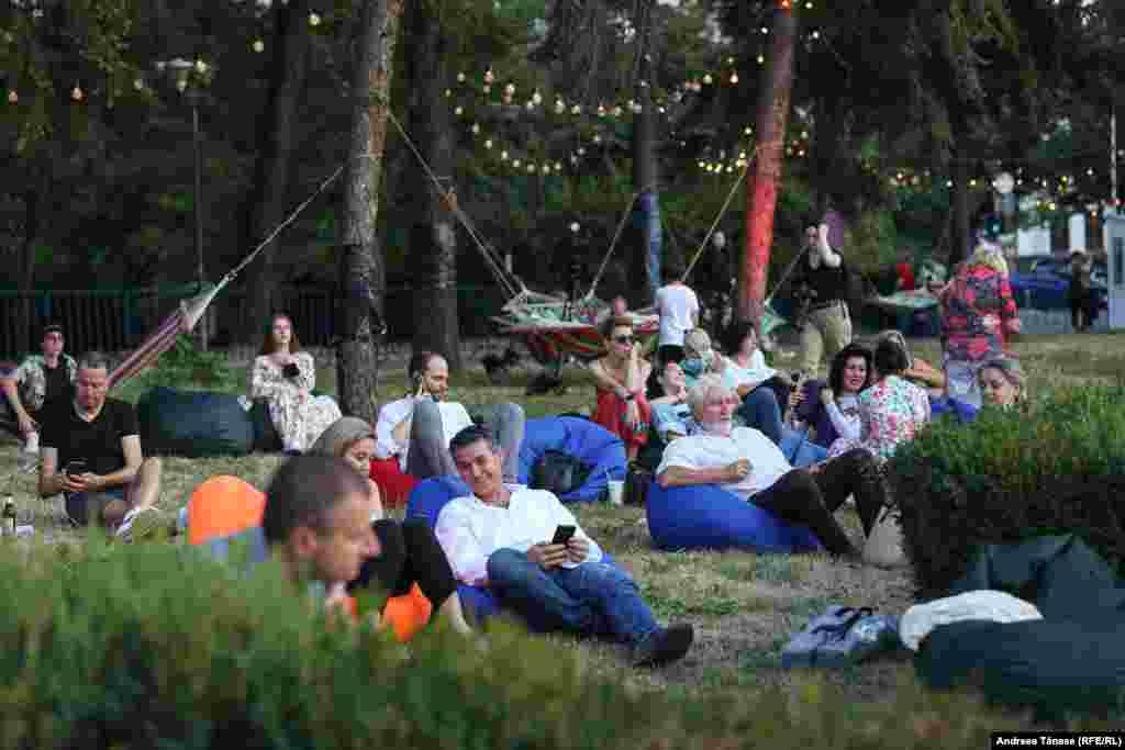 """Mai multe persoane se relaxează înaintea galei extraordinare de deschidere a festivalului """"Promenada Operei""""."""