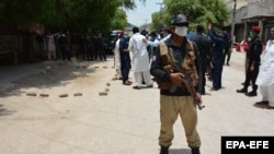 Pakistani security officials stand guard at a the scene of a blast in Ghotki, Sindh Province on June 19.