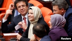 Депутаты от правящей партии Турции Нурджан Далбудак (в центре) и Севда Беязыт Каджар впервые присутствуют на сессии парламента в хиджабах. Анкара, 31 октября 2013 года.