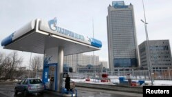 A Gazprom Neft gas station in Moscow with Gazprom headquarters in the background