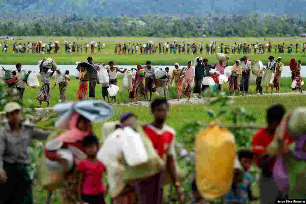 Rohingya refugees, who crossed the border from Burma two days before, walk after they received permission from the Bangladeshi Army to continue on to refugee camps in Palang Khali, near Cox's Bazar, Bangladesh. (Reuters/Jorge Silva)