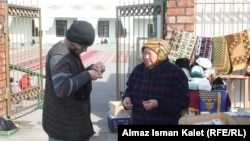 A trader outside a mosque in Bishkek