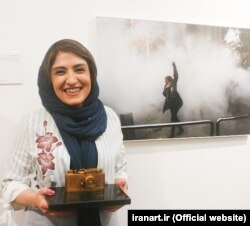 Yalda Moayeri poses with her photograph.