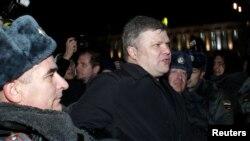 """Сайлау барысына қарсы шеруге қатысқан """"Яблоко"""" партиясының жетекшісі Сергей Митрохинді полиция тұтқындап жатыр. Мәскеу, 6 желтоқсан 2011 жыл."""