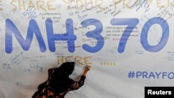 Malaysia -- A woman writes a message of support and hope for the passengers of the missing Malaysia Airlines MH370 on a banner at Kuala Lumpur International Airport March 12, 2014