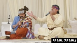 """Two musicians perform a """"music-less song"""" at a wedding party in Herat Province."""