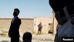 Авганистан - Талибански војник стои на стража пред куќа во соседство на засолниште на Исламската држава, нападнато од талибанските сили во северниот дел на Кабул. 4 октомври 2021 година.