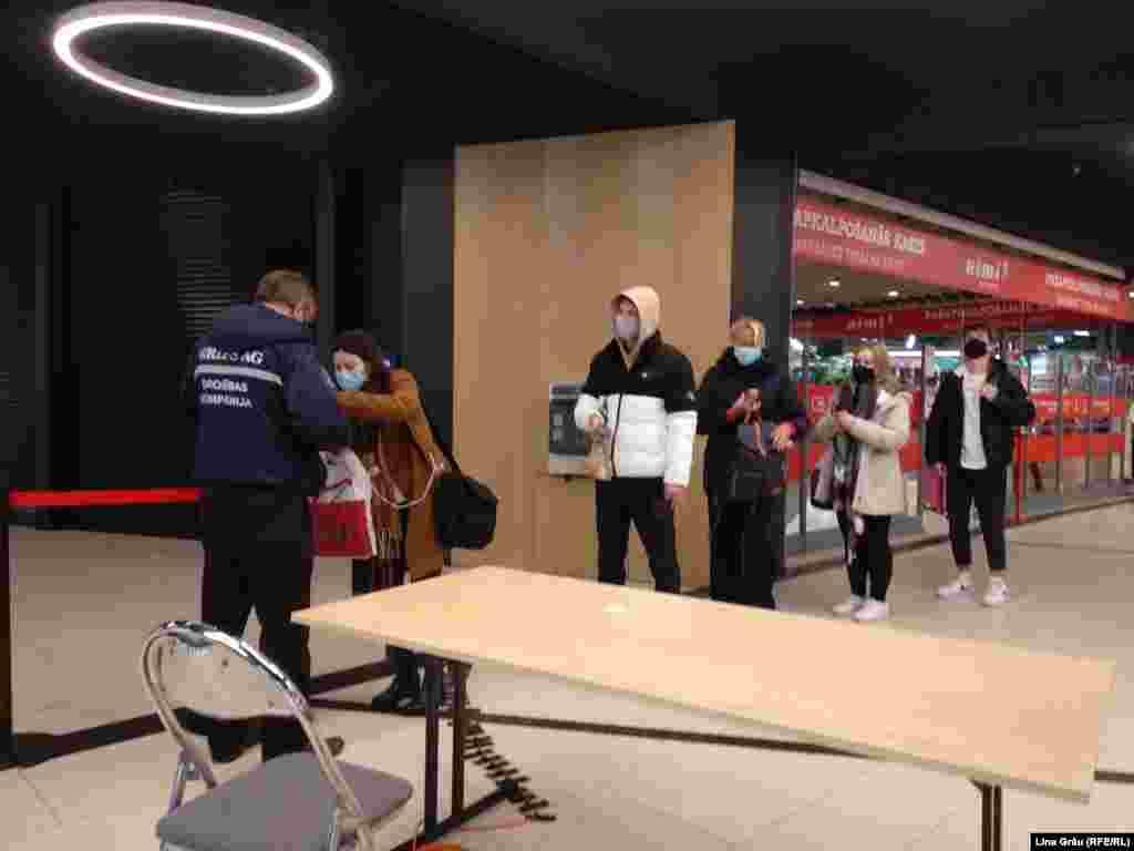 Agenții de securitate de la intrarea într-un mall din Riga spun că majoritatea respecta noile reglementări.