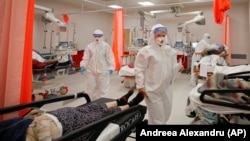 Patients lie on beds in the emergency room, turned into a COVID-19 unit due the high number of cases, at a hospital in Bucharest on October 12.