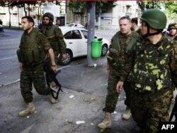 Министр обороны Давид Кезерашвили (первый слева) в Гори после российской бомбежки. 12 августа 2008 г.