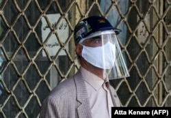 An Iranian man wearing personal protective equipment shops at the Grand Bazaar in the capital, Tehran.