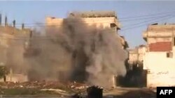 A photo from a video grab shows shells hitting a building in the neighborhood of Baba Amr in the flashpoint city of Homs on February 21.