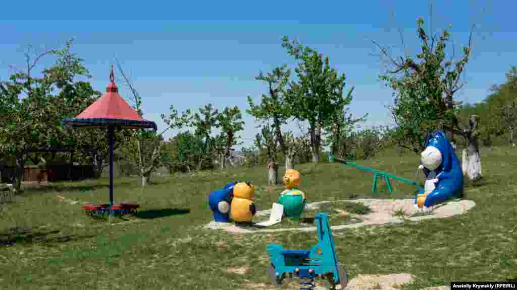 Мультяшный ослик Иа на детской площадке в старом черешневом саду перед фермой