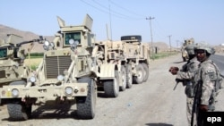 U.S. soldiers inspect the scene of a suicide car bomb attack in Kandahar in May.