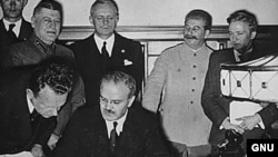 Foreign Minister Vyacheslav Molotov signs the pact. Behind him are Ribbentrop and Stalin