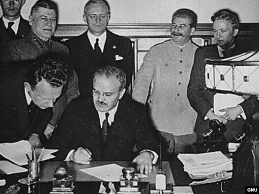 Soviet Foreign Minister Vyacheslav Molotov signs the German–Soviet non-aggression pact. Behind him are Ribbentrop and Stalin (Photo: rferl.org)