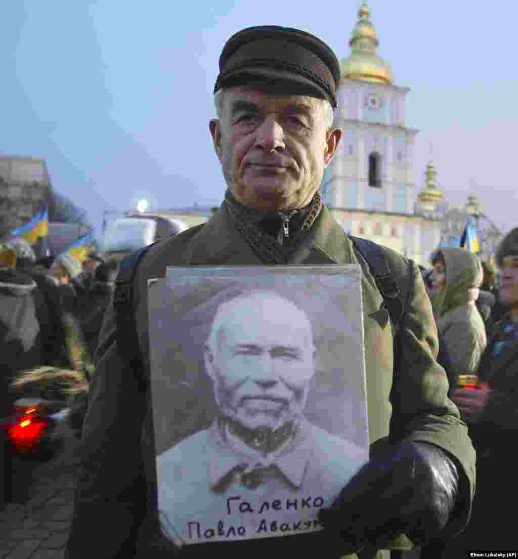 Viktor Golenko din satul Romnî, la o acțiune comemorativă în capitala Ucrainei, în noiembrie 2005, ținând fotografia tatălui său Pavlo, care a murit în perioada Holodomorului, în 1932.