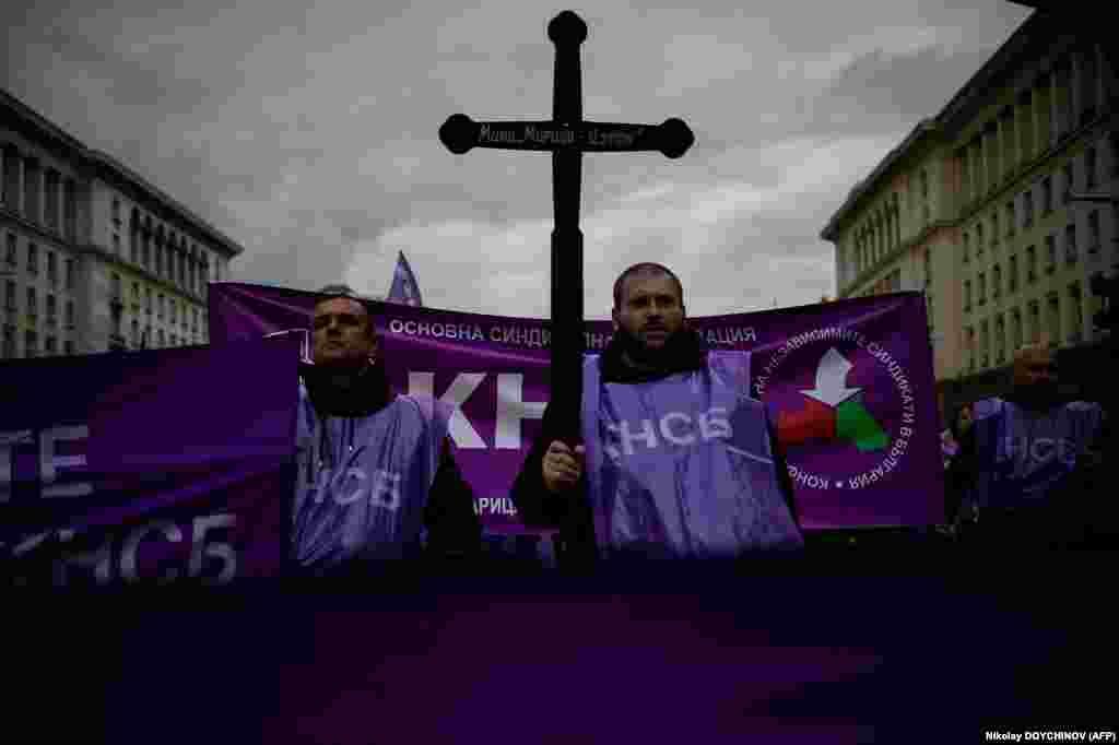Демонстрант в Софии 13 октября держит деревянный крест во время акции протеста против планов правительства Болгарии закрыть угольные электростанции в стране