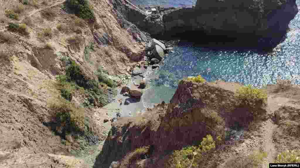 На небольшом пляже у мыса Лермонтова загорают люди, температура воздуха днем +18-19 градусов Цельсия