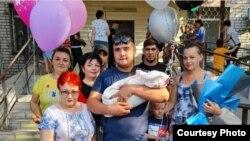 Житель Семея Руслан Карашев в окружении близких стоит с ребенком на руках после выписки жены из роддома