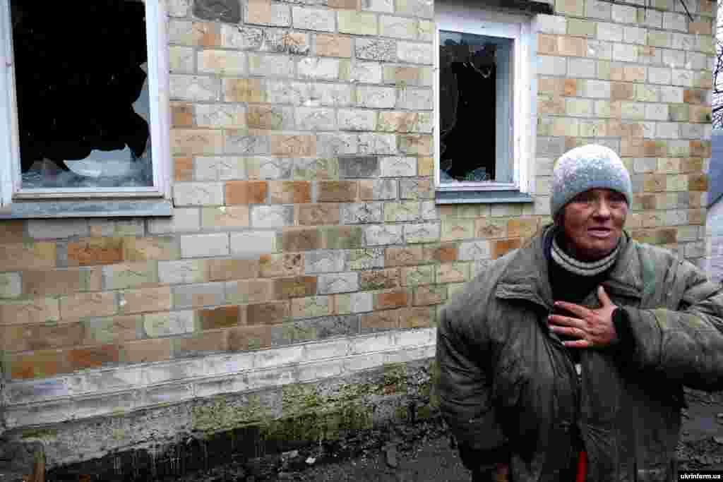 Жінка біля житлового будинку, пошкодженого в результаті артобстрілу, смт Зайцеве, Донецька область, 14 березня 2016 року
