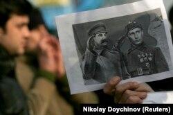 Протест у Болгарії проти будівництва трубопроводу з Росією. Учасник акції тримає колаж, на якому забражено Путіна поруч зі Сталіним. Софія, 2008 рік