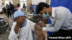 په پاکستان کې یو روغتیاپال یو کس ته د کووېډ-۱۹ چینايي واکسین لګوي.