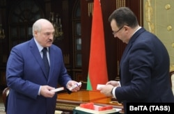 Belarusian Health Minister Dzmitry Pinevich (right) presents a batch of Russian Sputnik V vaccine to Alyaksandr Lukashenka in Minsk earlier this year.