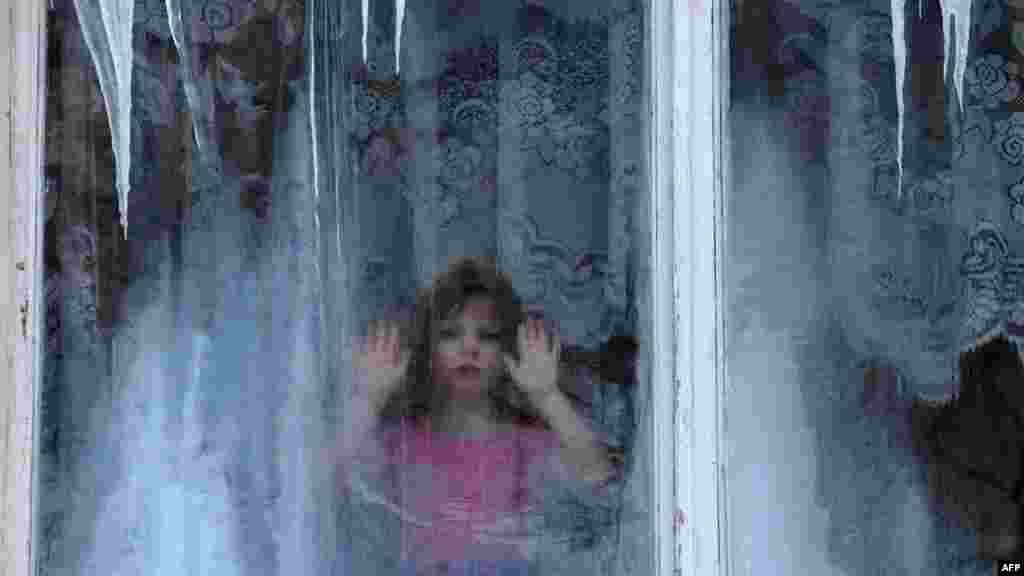 A girl looks through the ice-covered window of a kindergarten in Minsk. (AFP/Victor Drachev)