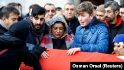 Relatives mourn at the funeral of Ayhan Arik, a victim of the Istanbul nightclub attack.