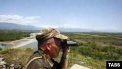 A Russian border guard patrols Abkhazia's border with Georgia proper near the bridge across the Inguri River.