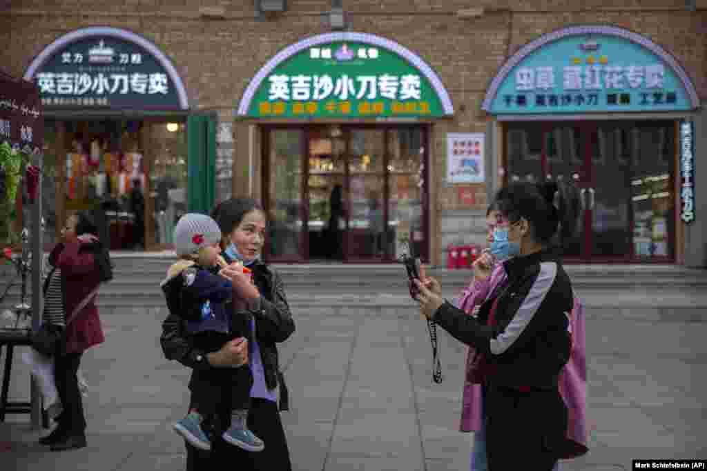 China Xinjiang Daily Life -- A woman poses for a smartphone photo with a child at the International Grand Bazaar in Urumqi in western China's Xinjiang Uyghur Autonomous Region, as seen during a government organized trip for foreign journalists, Wednesday,