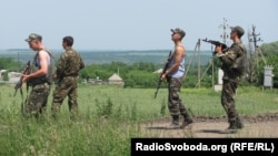 """Ukrainian military equipment and soldiers at a checkpoint in the area of a """"counterterrorist operation"""" on the road between Izyum and Slovyansk on June 10."""