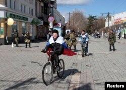 Мальчик с российским флагом на плечах едет на велосипеде. Город Симферополь, 17 марта 2014 года.