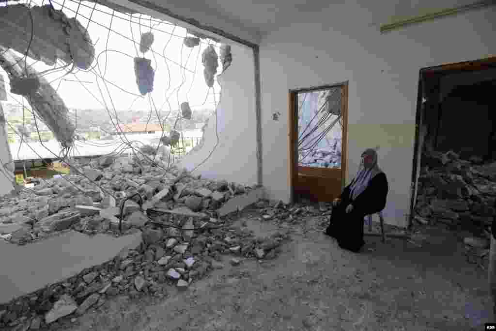 Palestinian mother Bilal Abu Zaid inspects what is left of her home after it was reportedly demolished by Israeli troops in the West Bank village of Qabatya, near Jenin. (epa/Alaa Badarneh)