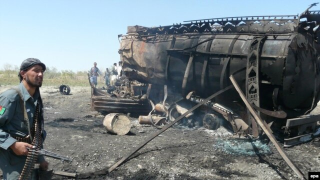 Afghan Police inspect the burned-out oil tankers at the site of the NATO-led air strike in Konduz on September 4.