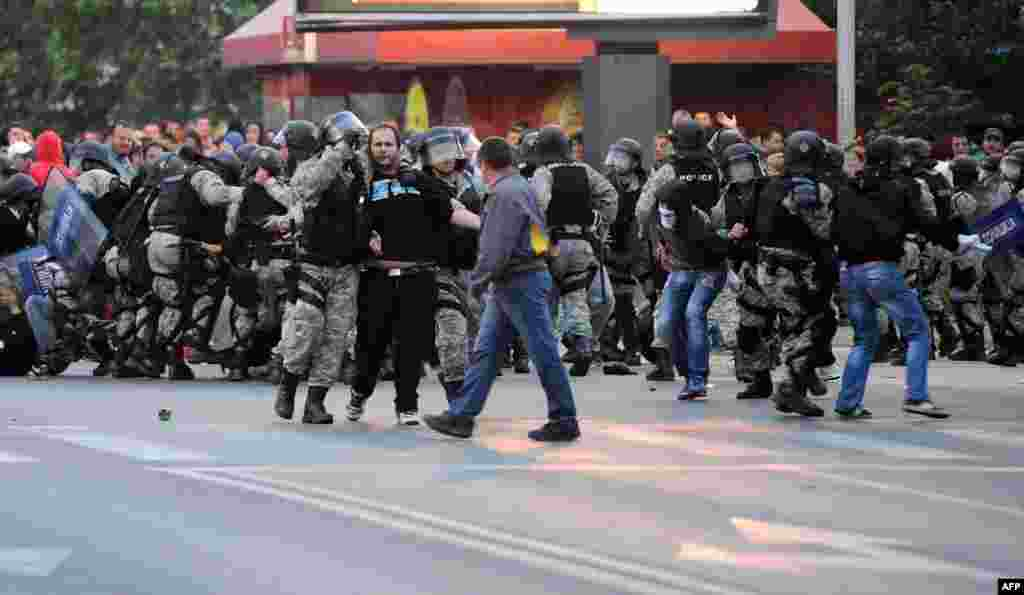Riot police scuffle with protesters.
