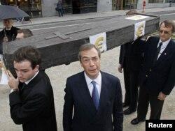 """Лидер Партии Независимости Соединенного Королевства Найджел Фарадж во время демонстрации в Брюсселе с требованием прекратить помощь ЕС Греции - у гроба, символизирующего """"смерть евро"""""""
