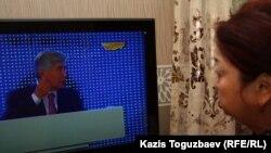 """Теледидардан """"Хабар"""" телеарнасын көріп отырған әйел. Алматы. (Көрнекі сурет)."""