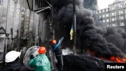 Протестующие жгут покрышки в центре Киева, чтобы преградить путь сотрудникам спецподразделений милиции. 25 января 2014 года.