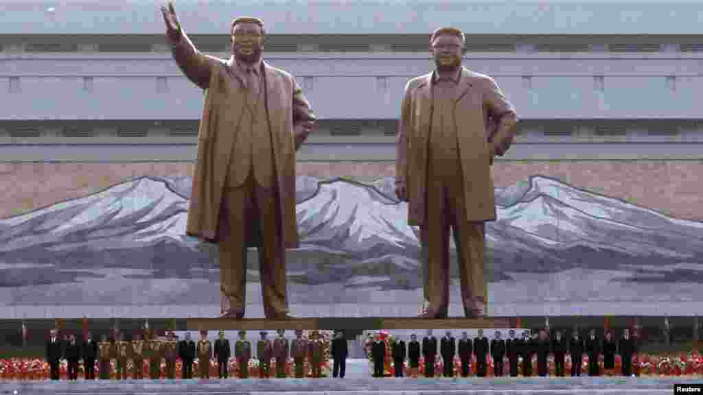North Korean leader Kim Jong Un stands with military officers and government officials during the unveiling ceremony on April 13 of bronze statues of his grandfather, Kim Il Sung (left statue), and his father, Kim Jong Il, in Pyongyang. (Reuters/Bobby Yip