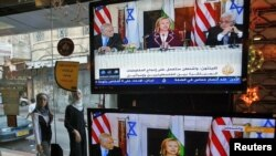 Women walk outside an electronics shop in the West Bank city of Ramallah during a TV broadcast showing Binyamin Netanyahu, U.S. Secretary of State Hillary Clinton, and Mahmud Abbas on September 2.