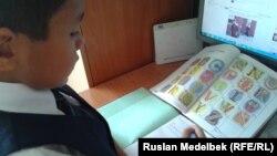 Ученик начальных классов с учебником английского языка. Алматы, 5 сентября 2013 года.