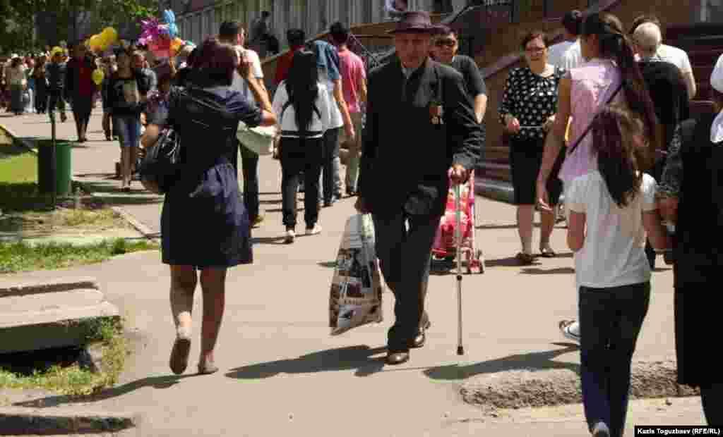 Ветеран войны идет среди прохожих. Алматы, 9 мая 2013 года.