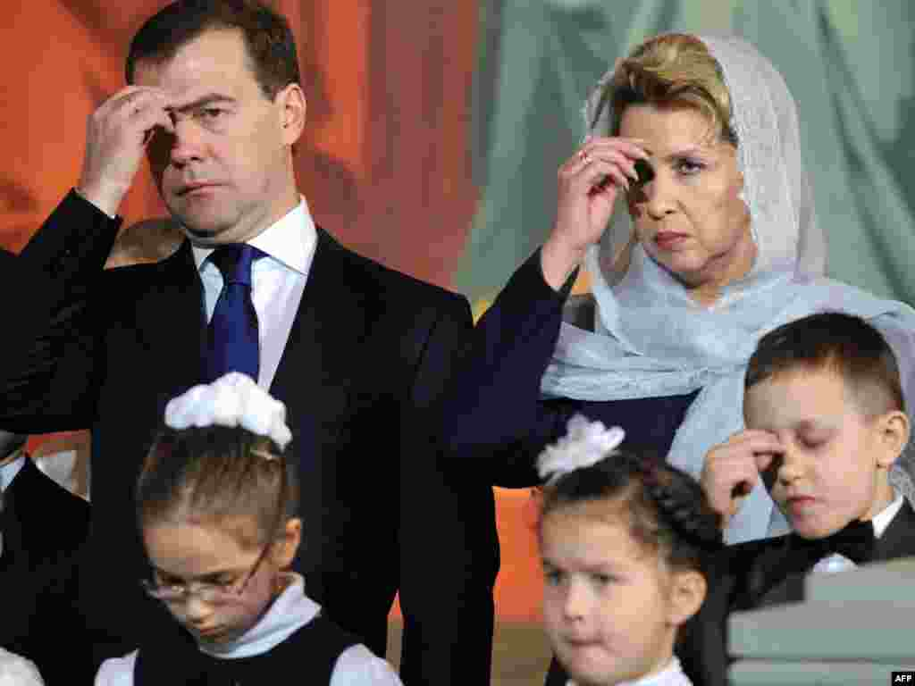 In Moscow, Russian President Dmitry Medvedev and his wife Svetlana cross themselves during a service on Christmas Eve.