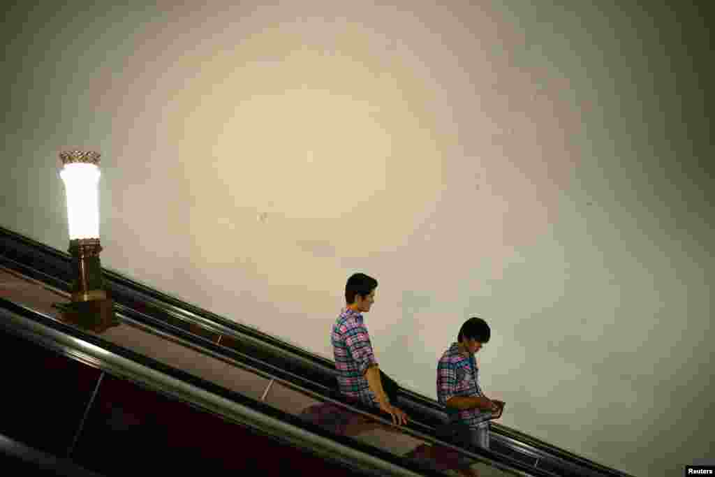 Two men go down an escalator at a Moscow metro station.