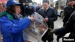 "A woman hands out free newspapers with the headline ""Crimea Chooses Russia"" on a street in Simferopol, the Crimean republic's capital, on March 17."